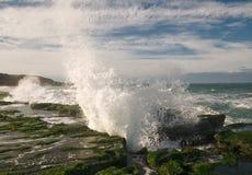 Spritzen der Welle auf Steingraben Stockfotos