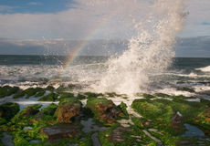 Spritzen der Welle auf Steingraben mit Regenbogen Lizenzfreie Stockfotos