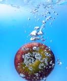 Spritzen des Apfels in ein Wasser Lizenzfreie Stockfotos