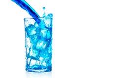 Spritzen des blauen Wassers in das Glas lokalisiert auf Weiß Stockbilder