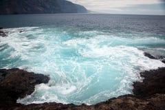 Spritzen des blauen Wassers nahe Küste Stockfotos