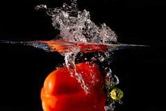 Spritzen des Gemüses auf Wasser Stockfotos