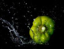 Spritzen des grünen Pfeffers Stockfotografie