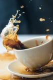 Spritzen des Kaffees im weißen Cup Lizenzfreies Stockfoto