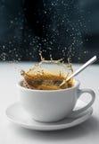Spritzen des Kaffees im weißen Cup Lizenzfreies Stockbild