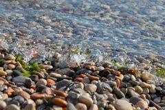 Spritzen des Meerwassers mit Tropfen auf Küstenkieseln Stockfoto