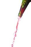 Spritzen des roten Wassers von der Flasche Stockbild