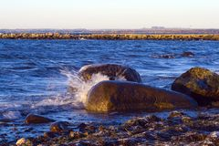Spritzen des Wassers auf Felsen Stockfotografie