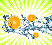 Spritzen des Wassers mit Orangen lizenzfreie stockfotos