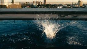 Spritzen des Wassers nach jemand sprang zum Wasser bei Sonnenuntergang an einem Dachspitzenpool lizenzfreie stockfotografie