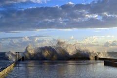Spritzen durch einen Wellenbrecher von einer Welle während eines Sturms stockfoto