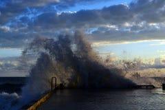 Spritzen durch einen Wellenbrecher von einer Welle während eines Sturms lizenzfreie stockbilder
