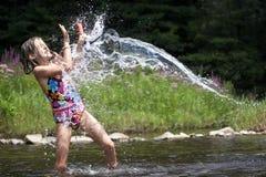 Spritzen! Ein junges Mädchen erhält durch Wasser getränkt Stockbilder