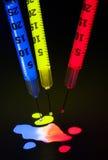 Spritzen mit Glühen-Stockflüssigkeit Stockfotografie