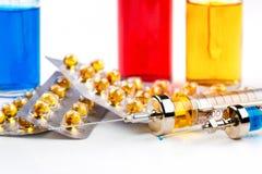 Spritzen mit Medikation, Blisterpackungen mit Pillen und Flaschen mit farbiger Flüssigkeit auf weißem Hintergrund Lizenzfreie Stockfotografie
