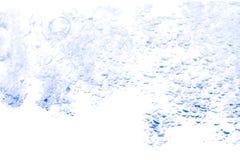 Spritzen Sie blaue Farbe des Wassers mit Blasen der Luft, auf weißem Hintergrund Stockfoto