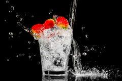 Spritzen Sie in einem Glas mit der Beere und dem Eis mit drei Rottönen Lizenzfreie Stockfotos