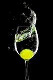 Spritzen Sie in einem Glas mit Zitronekugel auf einem Schwarzen Lizenzfreie Stockfotografie