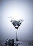 Spritzen Sie vom Eiswürfel in lokalisiertem Martini-Glas Stockbild