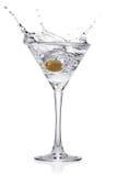 Spritzen Sie von der Olive in einem Glas des Cocktails. lizenzfreie stockbilder