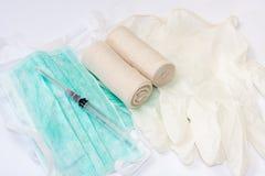 Spritzen und Verbände auf chirurgischer Maske und Handschuhen Stockbilder