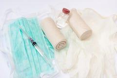 Spritzen und Verbände auf chirurgischer Maske und Handschuhen Stockbild