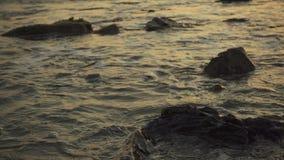 Spritzen von kleinen Wellen auf den Felsen an der Sonnenuntergangzeitlupe stock footage