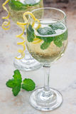 Spritzer cocktail with white wine, mint and ice, decorated with spiral lemon zest Royalty Free Stock Photography