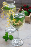 Spritzer cocktail with white wine, mint and ice, decorated with spiral lemon zest Stock Image