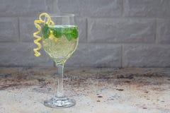 Spritzercoctailen med vitt vin, mintkaramell och is, dekorerade med spiral citronpiff, kopieringsutrymme Royaltyfri Foto