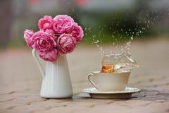 Spritzt vom Tee von einem weißen Becher, nahe bei einem Vase rosa Rosen I Stockbild