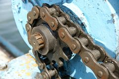 Sprocket and chain. A chain rotates on a sprocket powered by a motor to make the spindle turn royalty free stock images