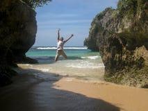 Sprong omhoog op een exotisch strand tussen de klippen die het overzees overzien stock foto's