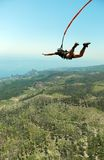 Sprong van een klip met een kabel Opgewekt meisje Royalty-vrije Stock Foto
