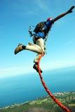 Sprong van een klip met een kabel Opgewekt meisje Stock Fotografie