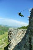 Sprong van een klip met een kabel Opgewekt meisje Stock Afbeelding