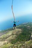 Sprong van een klip met een kabel Opgewekt meisje Royalty-vrije Stock Fotografie