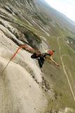 Sprong van een klip met een kabel Opgewekt meisje Stock Afbeeldingen