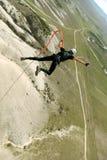 Sprong van een klip met een kabel Opgewekt meisje Royalty-vrije Stock Afbeeldingen