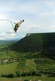 Sprong van een klip met een kabel Opgewekt meisje Stock Foto