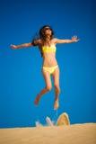 Sprong van het donkerbruine vrouwen de gele zwempak Stock Foto