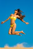 Sprong van het donkerbruine vrouwen de gele zwempak Stock Foto's