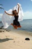 Sprong voor Vreugde bij strand Stock Afbeeldingen