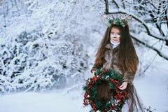 Sprookjemeisje Het portret een klein meisje in een hert kleedt zich met een geschilderd gezicht in de de winter bos Grote bruine  stock foto's