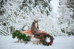 Sprookjemeisje Het portret een klein meisje in een hert kleedt zich met een geschilderd gezicht in de de winter bos Grote bruine  royalty-vrije stock afbeelding