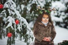 Sprookjemeisje Het portret een klein meisje in een hert kleedt zich met een geschilderd gezicht in de de winter bos Grote bruine  stock foto
