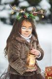 Sprookjemeisje Het portret een klein meisje in een hert kleedt zich met een geschilderd gezicht in de de winter bos Grote bruine  stock fotografie