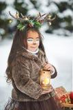 Sprookjemeisje Het portret een klein meisje in een hert kleedt zich met een geschilderd gezicht in de de winter bos Grote bruine  royalty-vrije stock fotografie