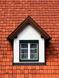 Spross Gaube roof window in a red roof. Gaube Spross roof with windows in a tile-covered roof Royalty Free Stock Image