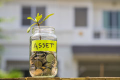 Sprout growing from coins in glass jar against blur house backge Stock Photos